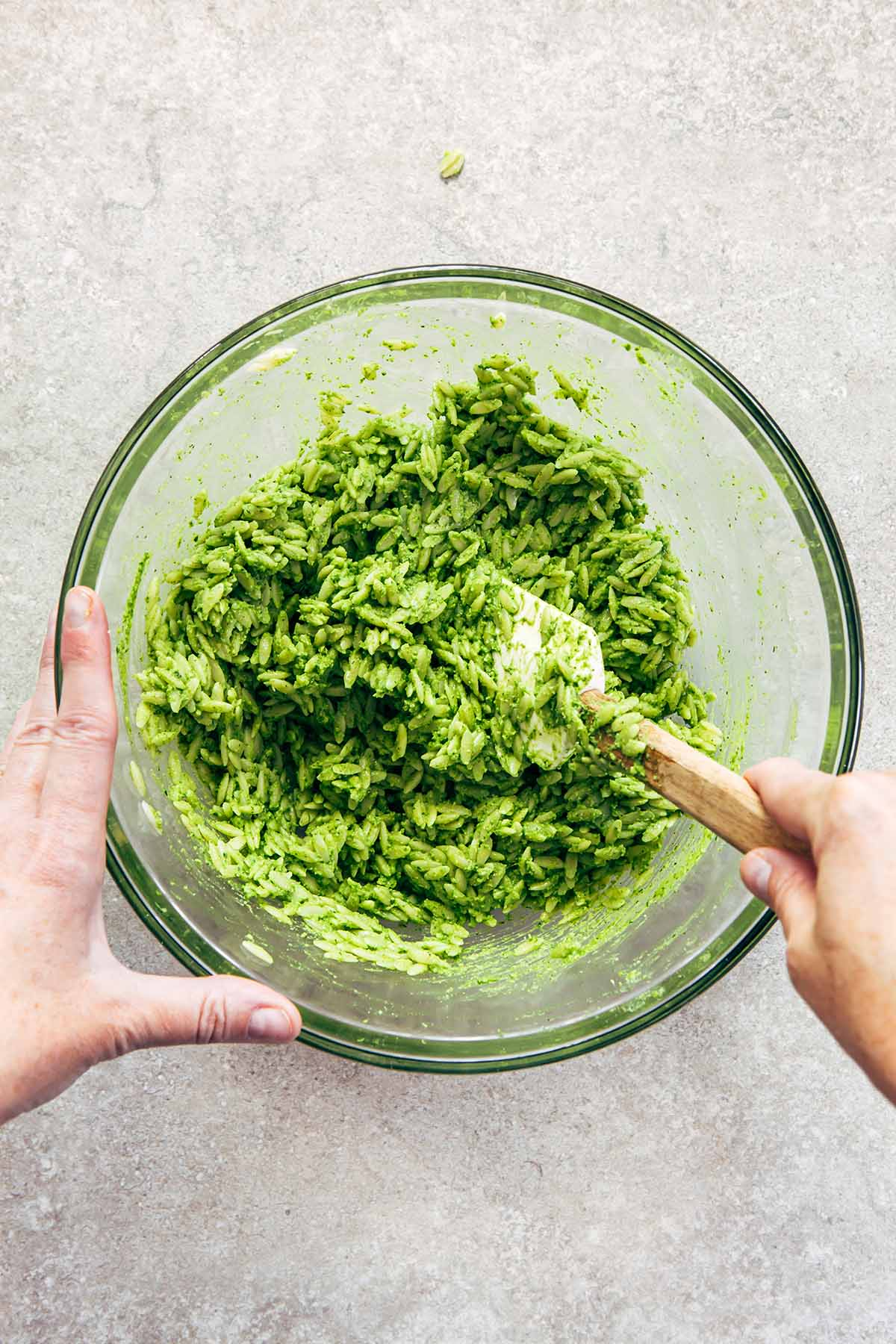 Hands stirring cooked orzo mixed with green pesto.