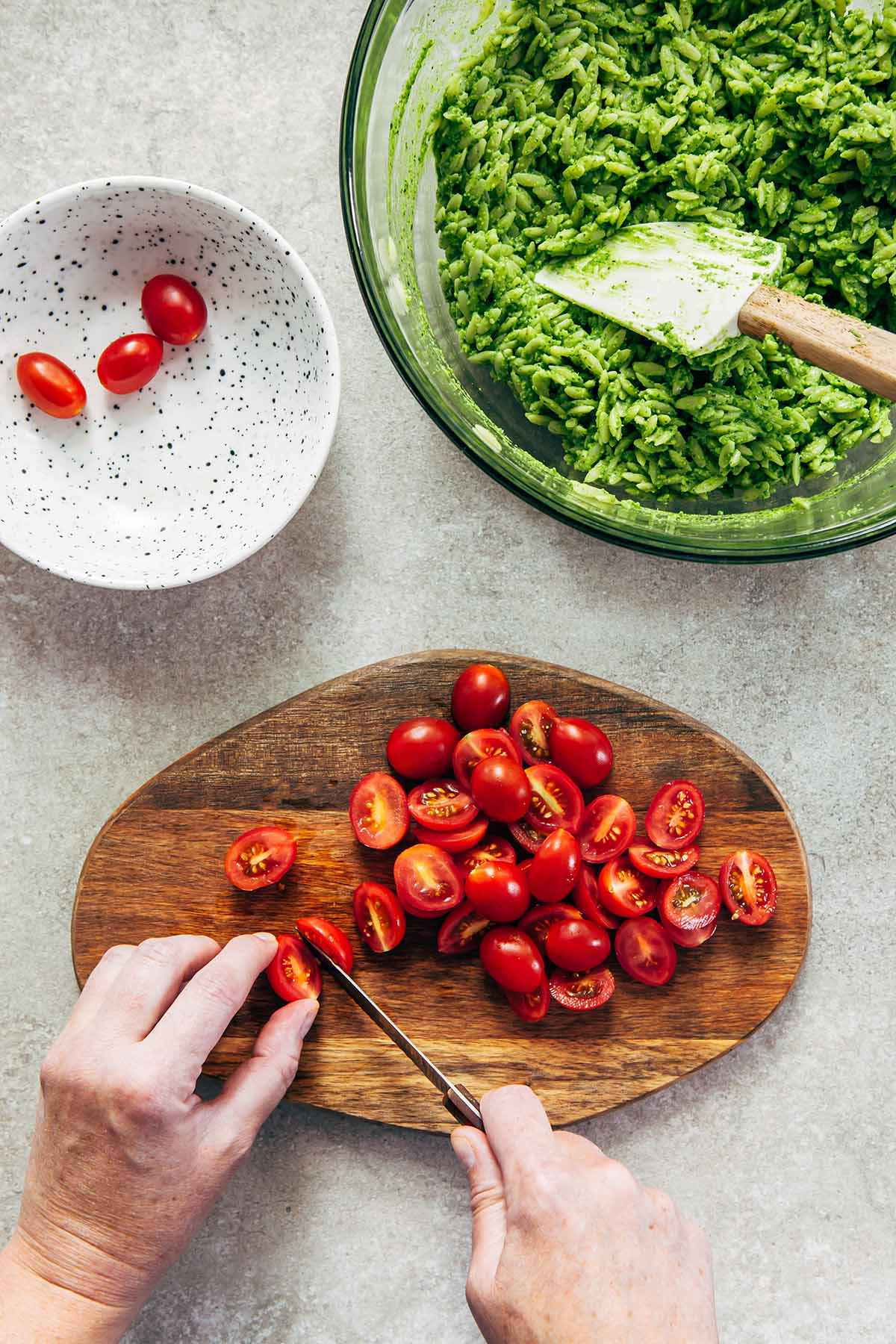 Hands slicing cherry tomatoes on a wooden board next to a small white bowl of tomatoes, and a larger bowl of cooked orzo with pesto.