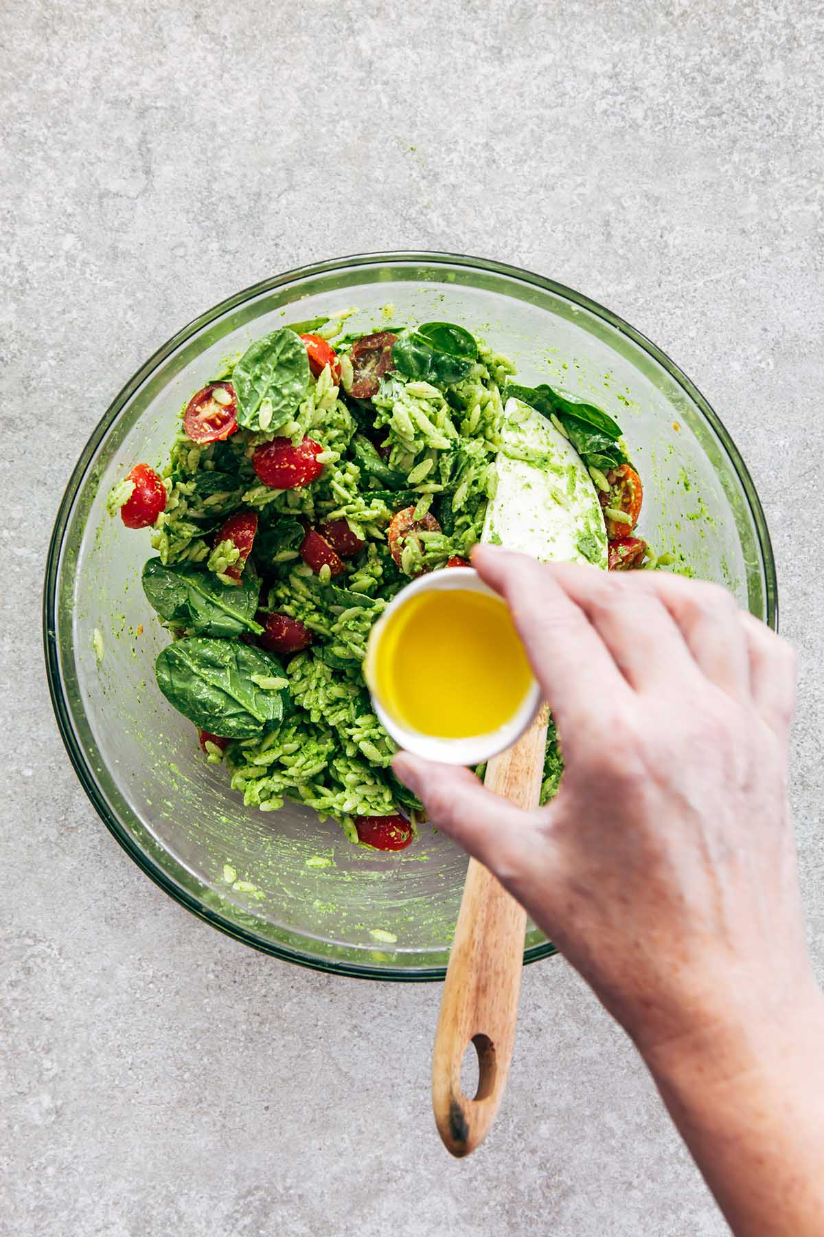 A hand drizzling olive oil from a small white bowl into a bowl of pesto orzo salad.