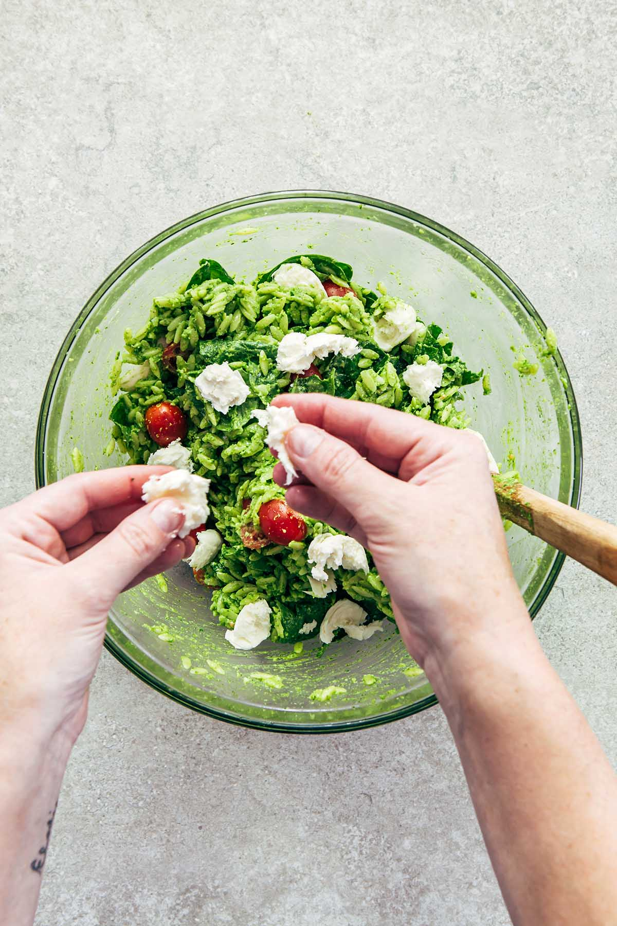 Hands tearing a ball of fresh mozzarella and adding the pieces to a bowl of pesto orzo salad.
