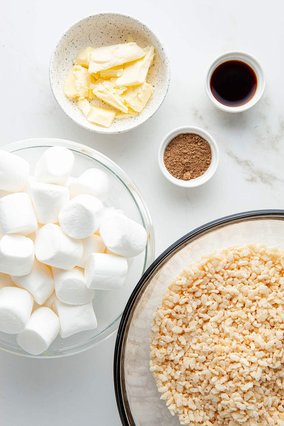 Ingredients to make chai-spiced Rice Krispie treats laid out on a white stone surface.