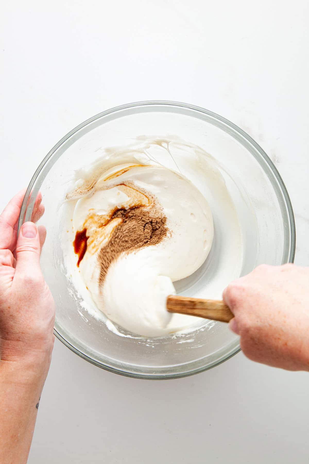 A hand mixing melted marshmallow, spices, and vanilla.