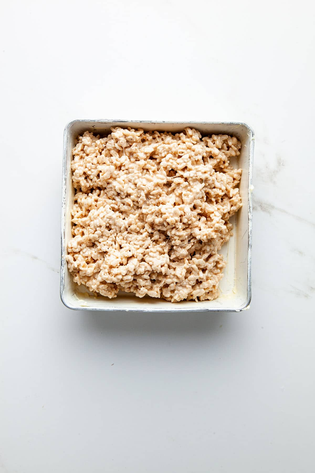 A pan of Rice Krispie treats before smoothing.