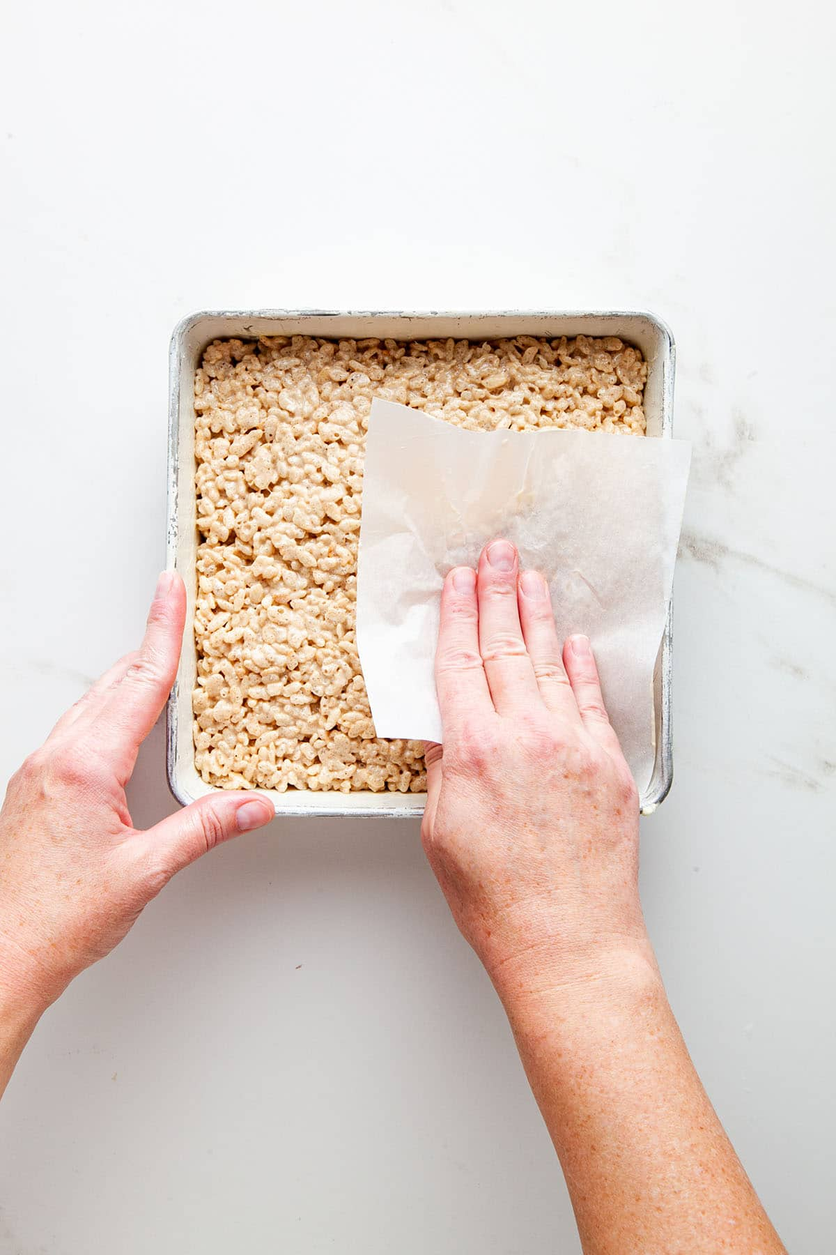 A hand smoothing the top of a pan of marshmallow treats with a small piece of parchment paper.