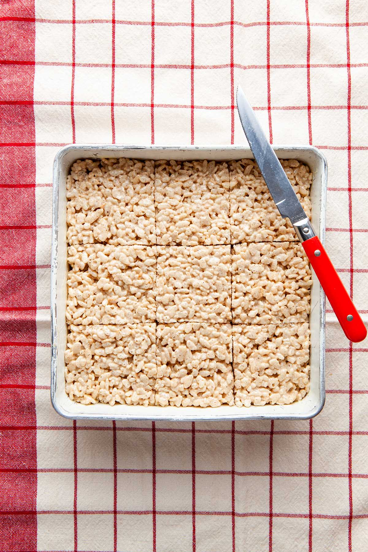 A pan of cut Rice Krispie squares with a red-orange-handled knife on a res checked tea towel.