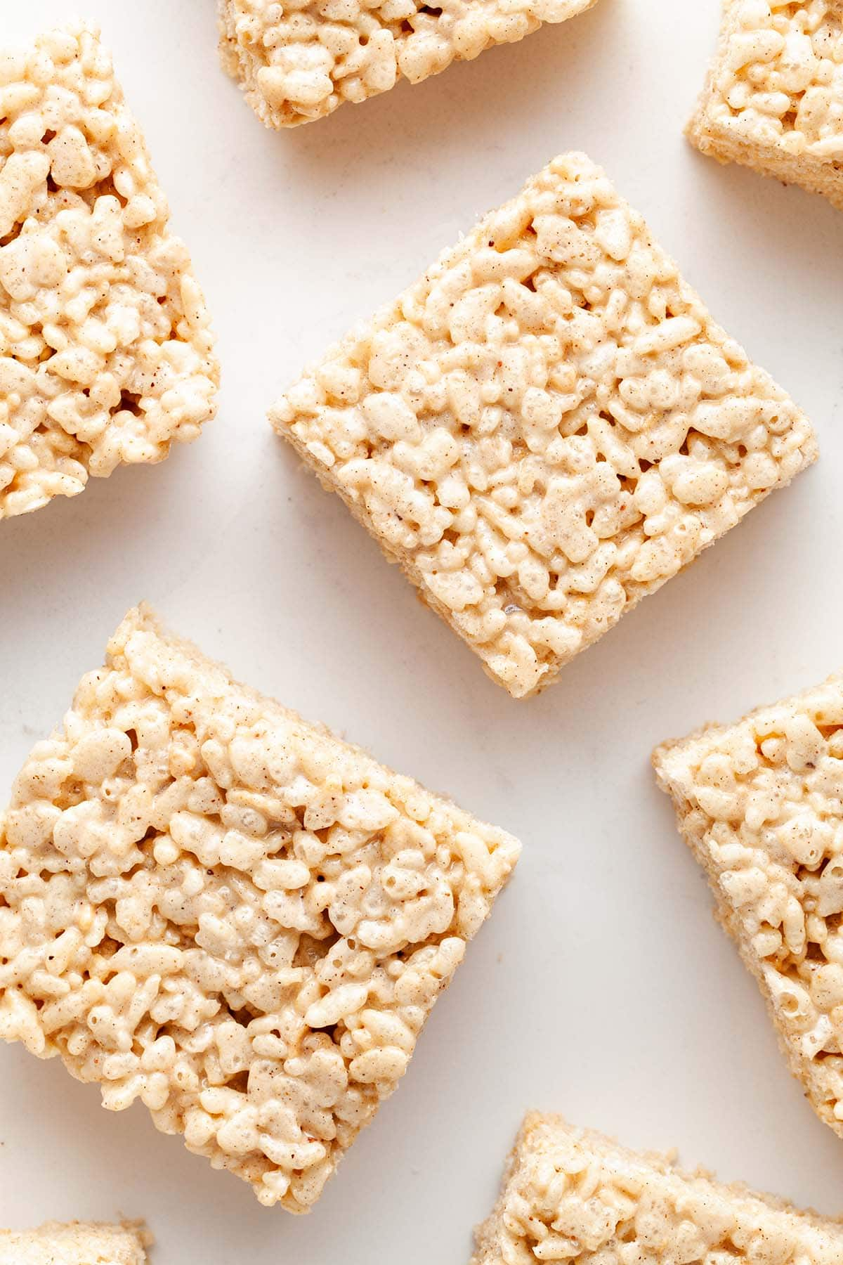 Rice Krispie squares laid out on a white surface.