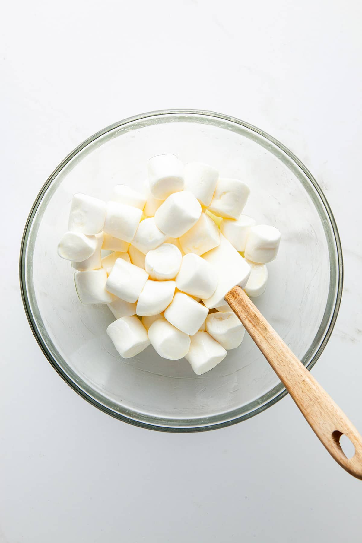 A glass bowl of marshmallows that have been stirred with melted butter.