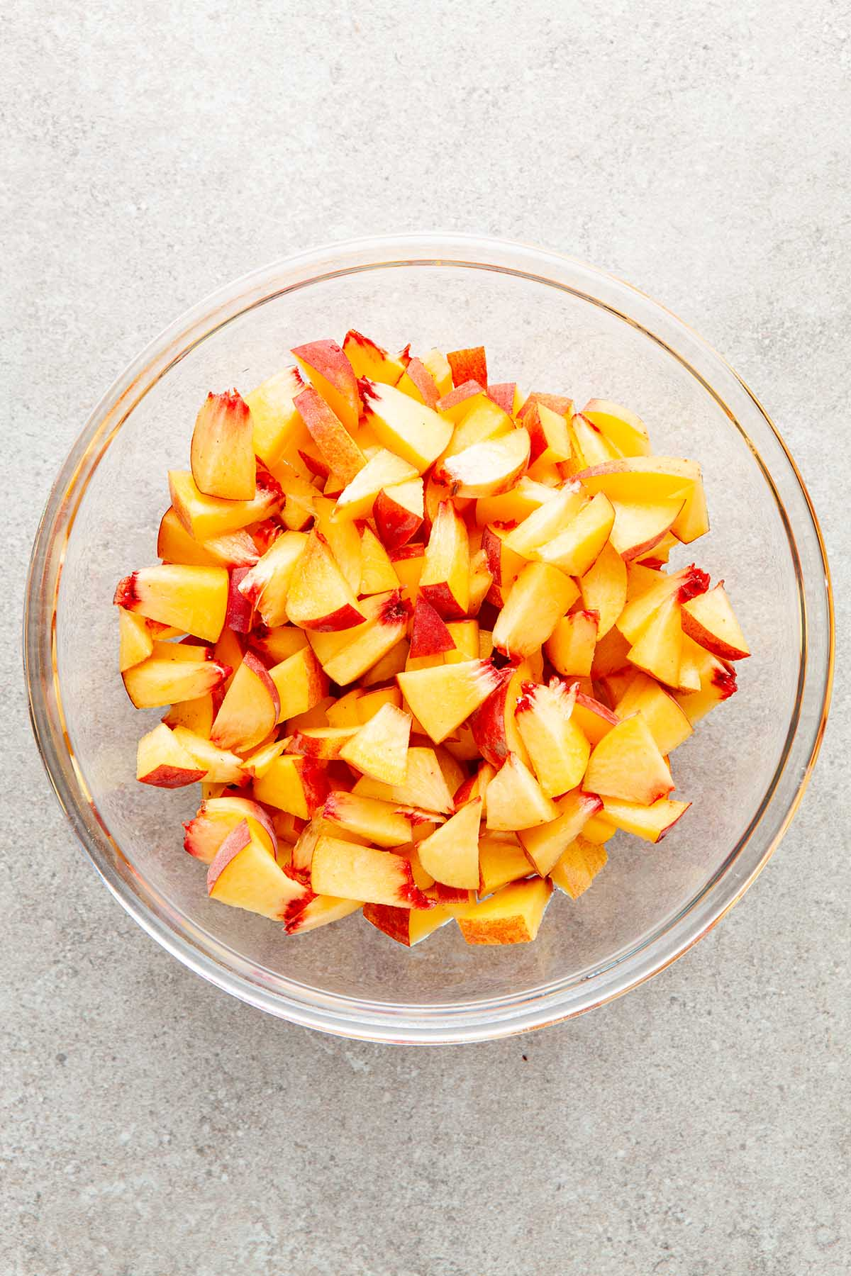 A glass bowl of chopped peaches.