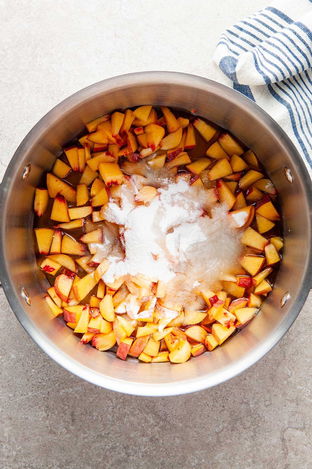 Chopped peaches, sugar, and maple syrup in a pot.
