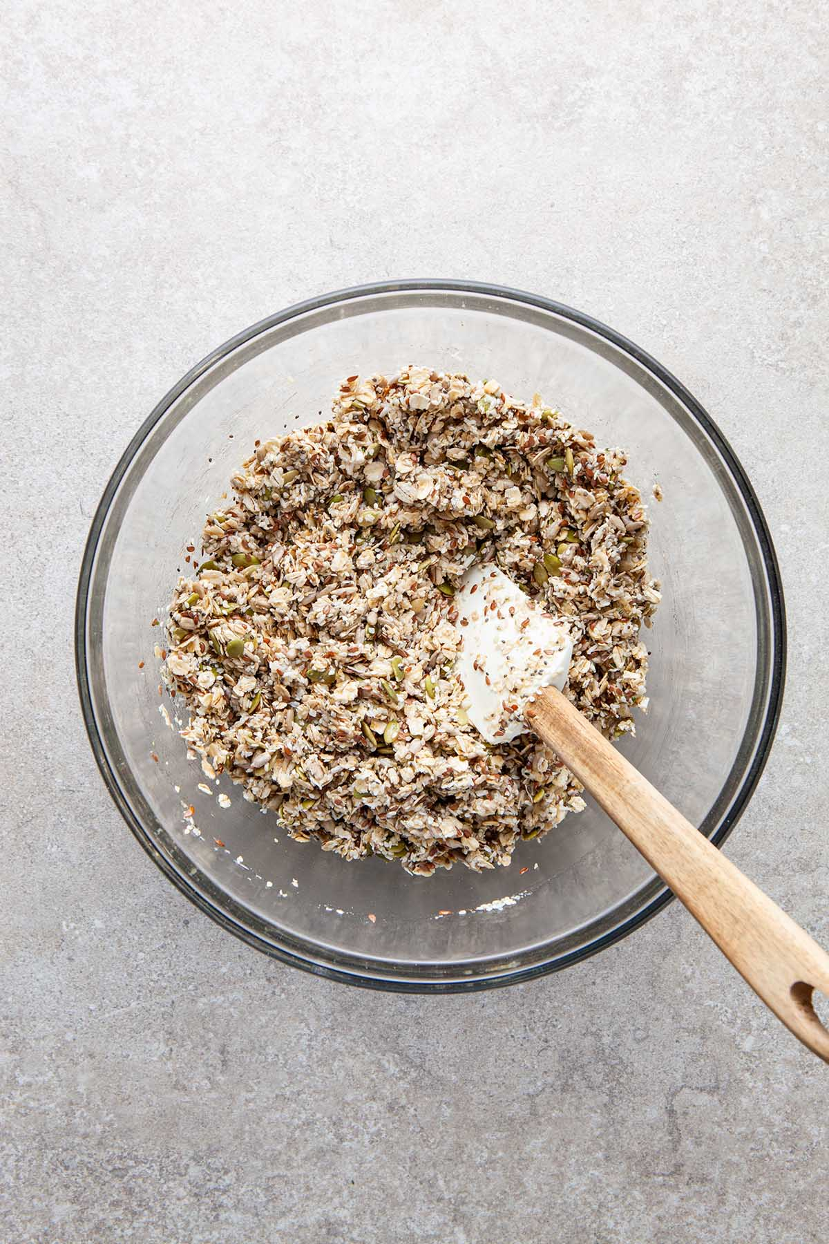 A glass bowl of oats, seeds, coconut, honey, and oil mixed together.