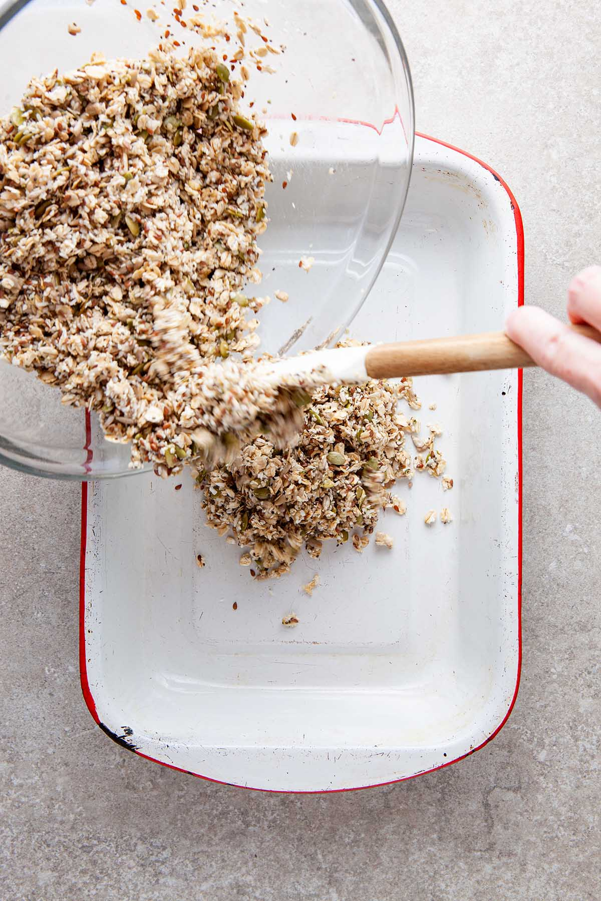 A hand scraping a honey, oat, and seeds mixture into a baking dish from a glass bowl.