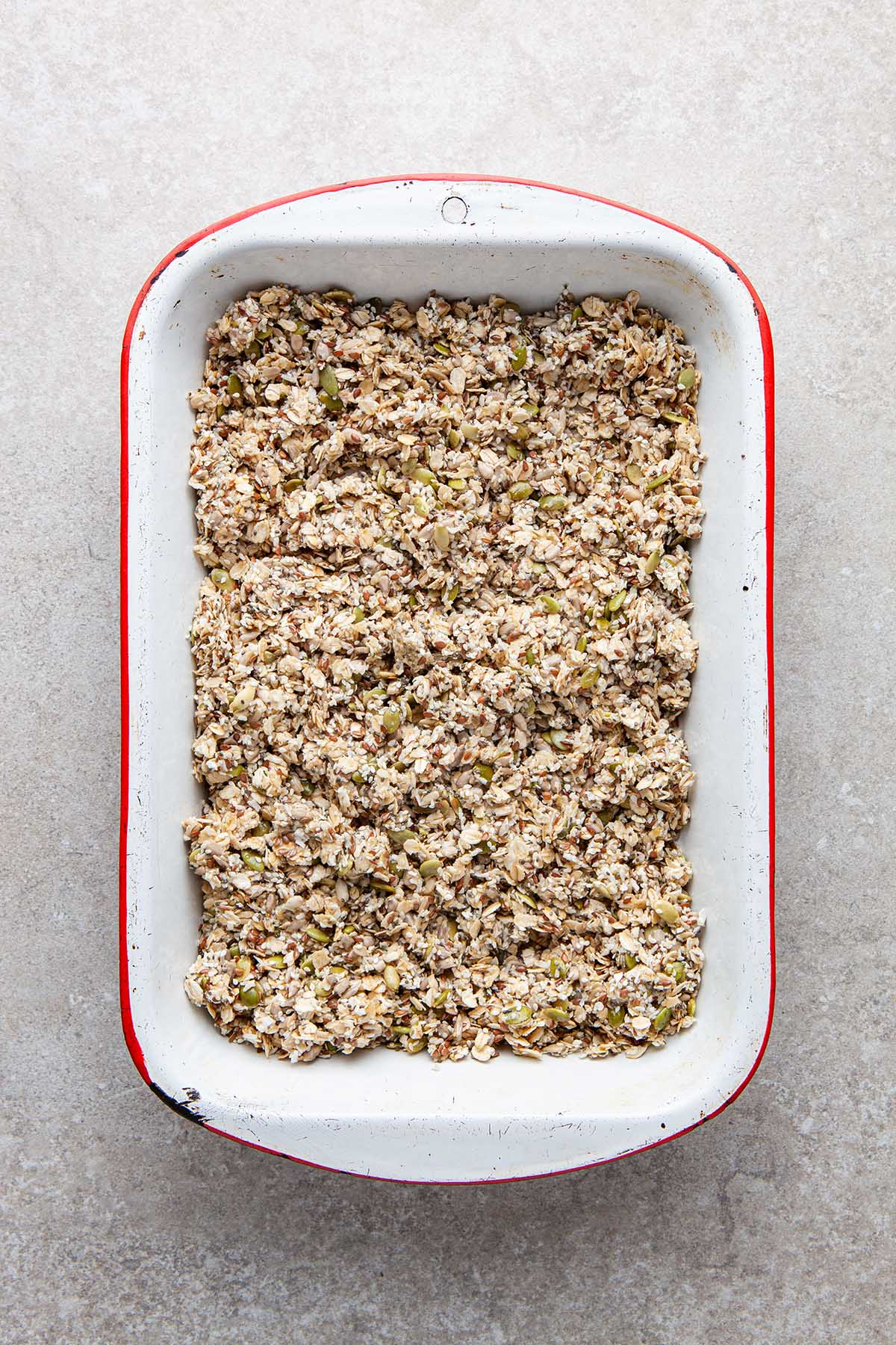 Unbaked granola in a deep white enamel baking dish with red trim.