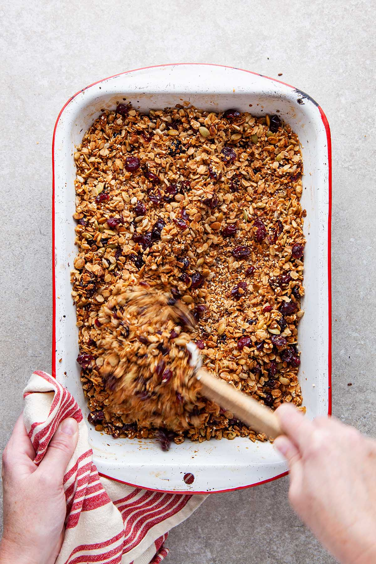 A hand stirring a baking pan filled with granola.