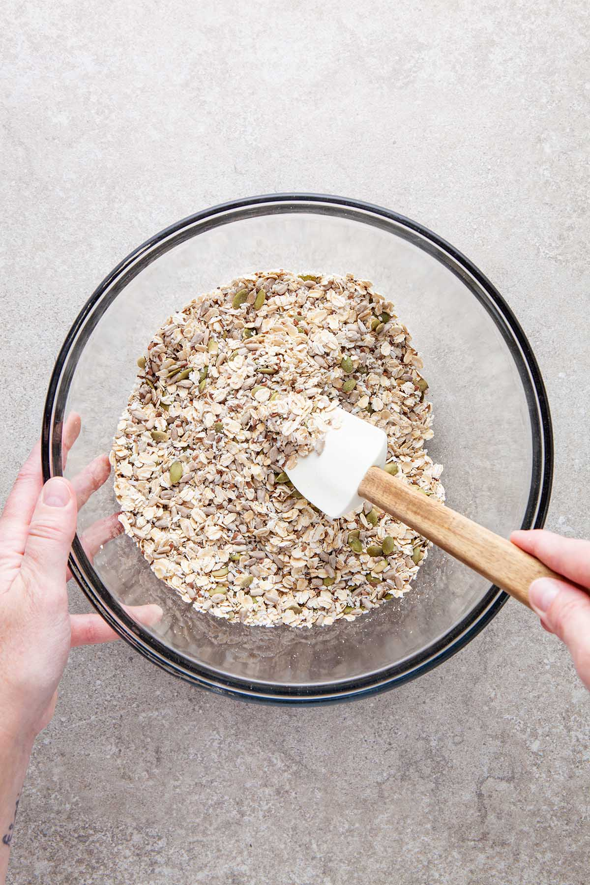 A hand mixing oats, seeds, and shredded coconut together.