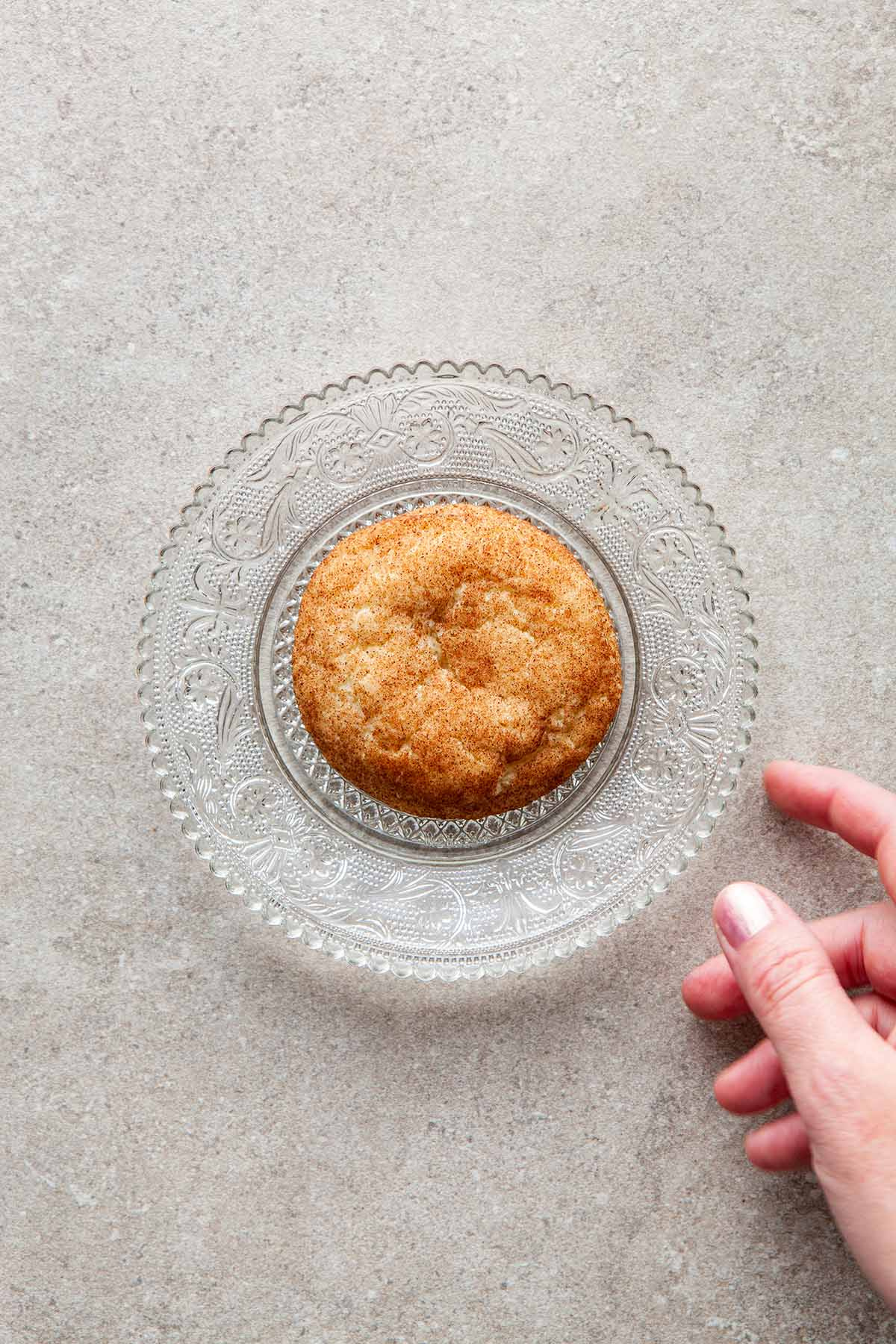 One cookie on a small glass plate with a hand reaching for the plate.