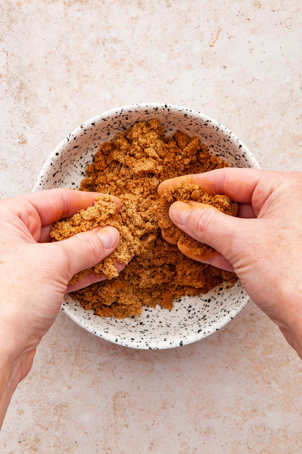 Hands smooshing brown sugar and cinnamon together in a white speckled bowl.