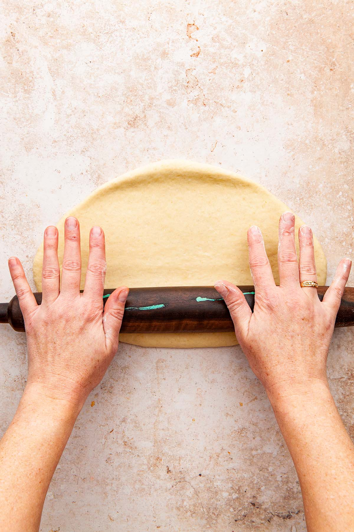Hands rolling dough with a pin.