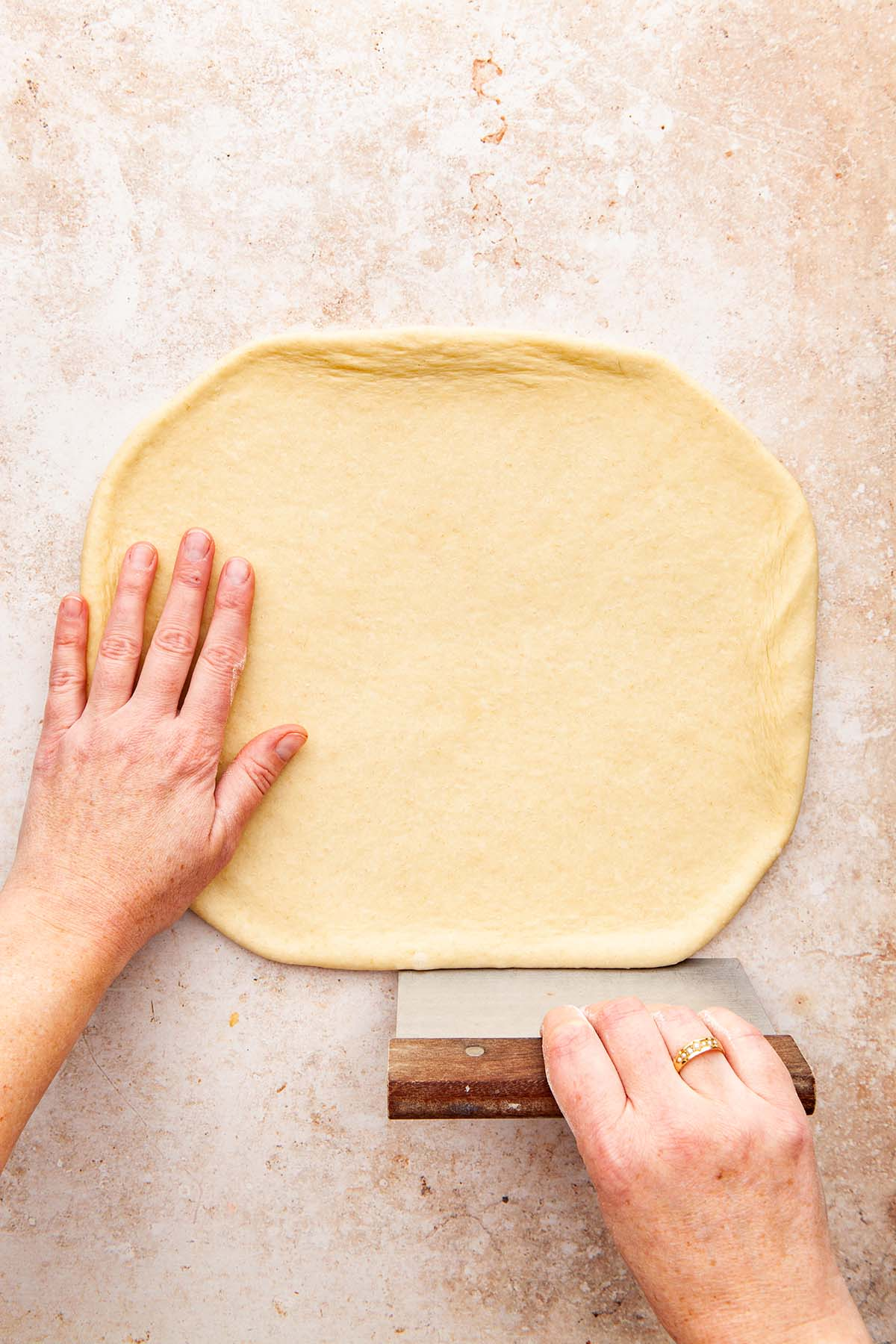 Hands straightening the sides of a rectangle of rolled out dough with a bench scraper.