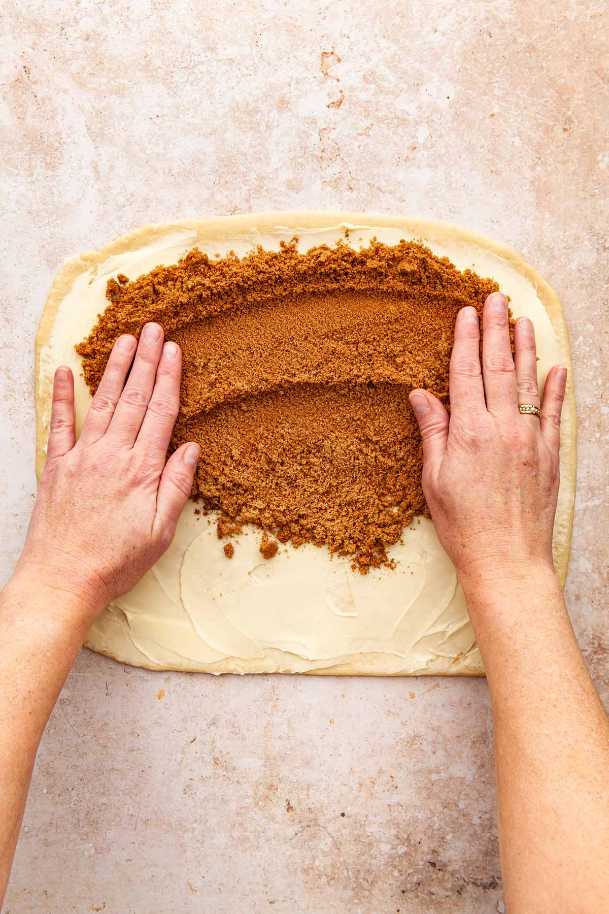 Hands spreading brown sugar and spice over a large rectangle of buttered dough.