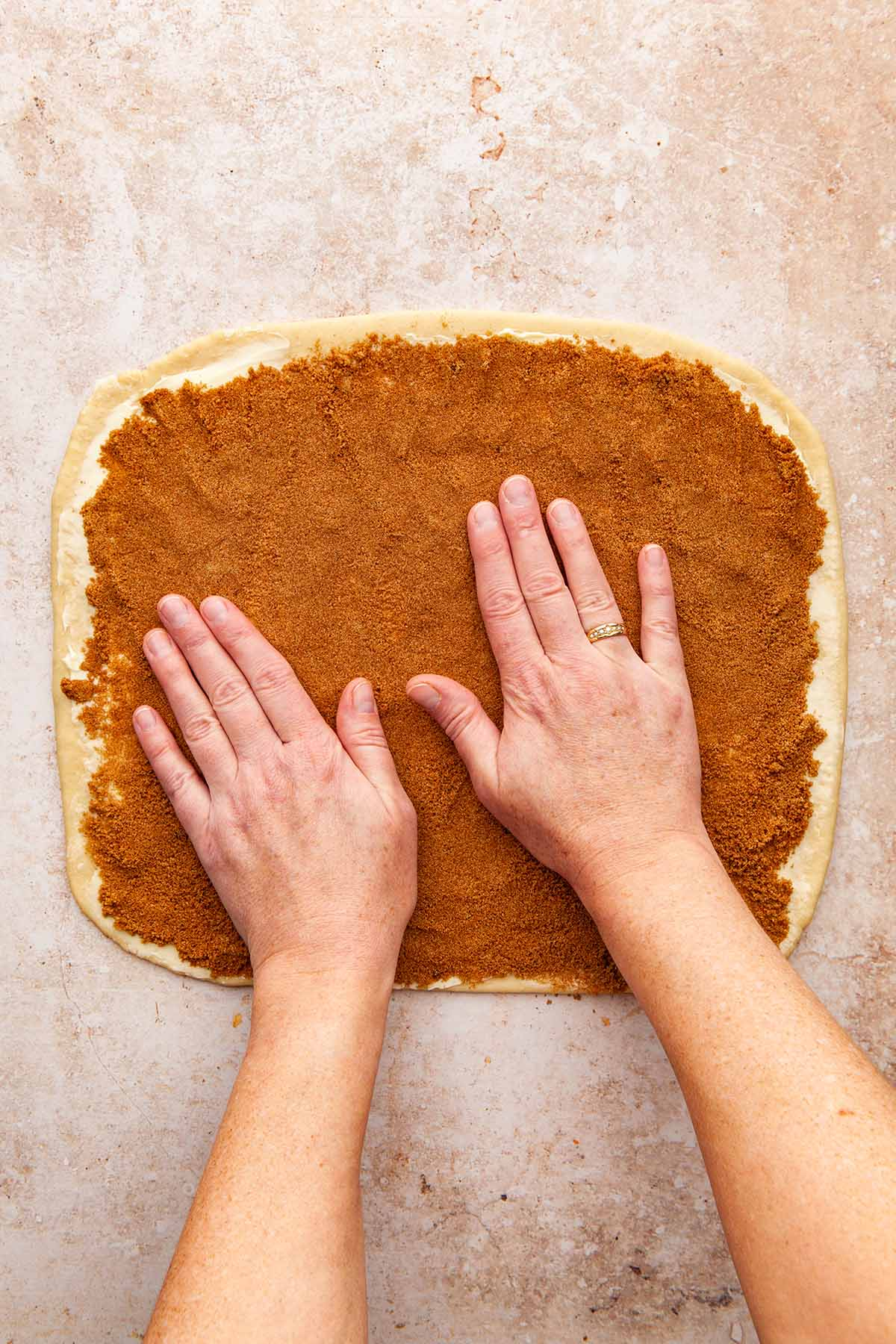 Hands pressing brown sugar and spice onto a large rolled out rectangle of dough.