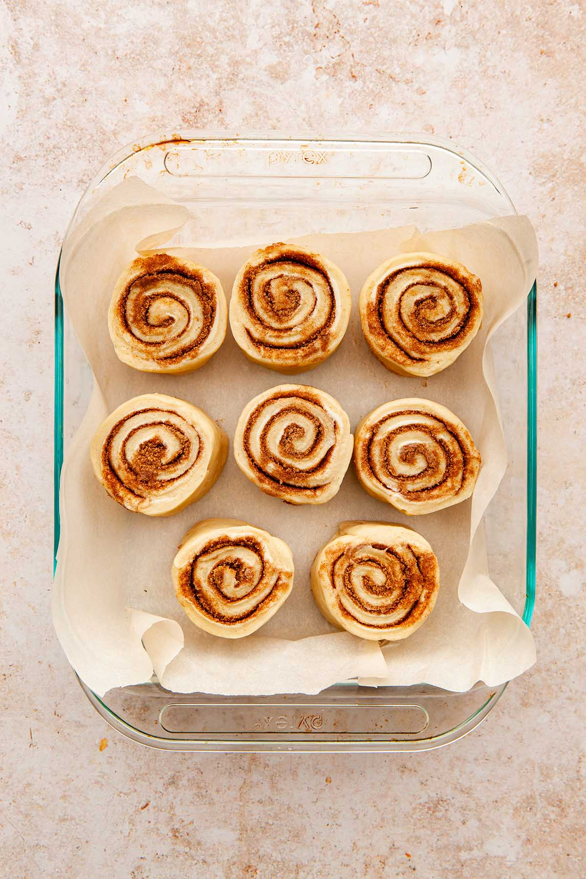 Cinnamon buns in a baking dish before the second rise.