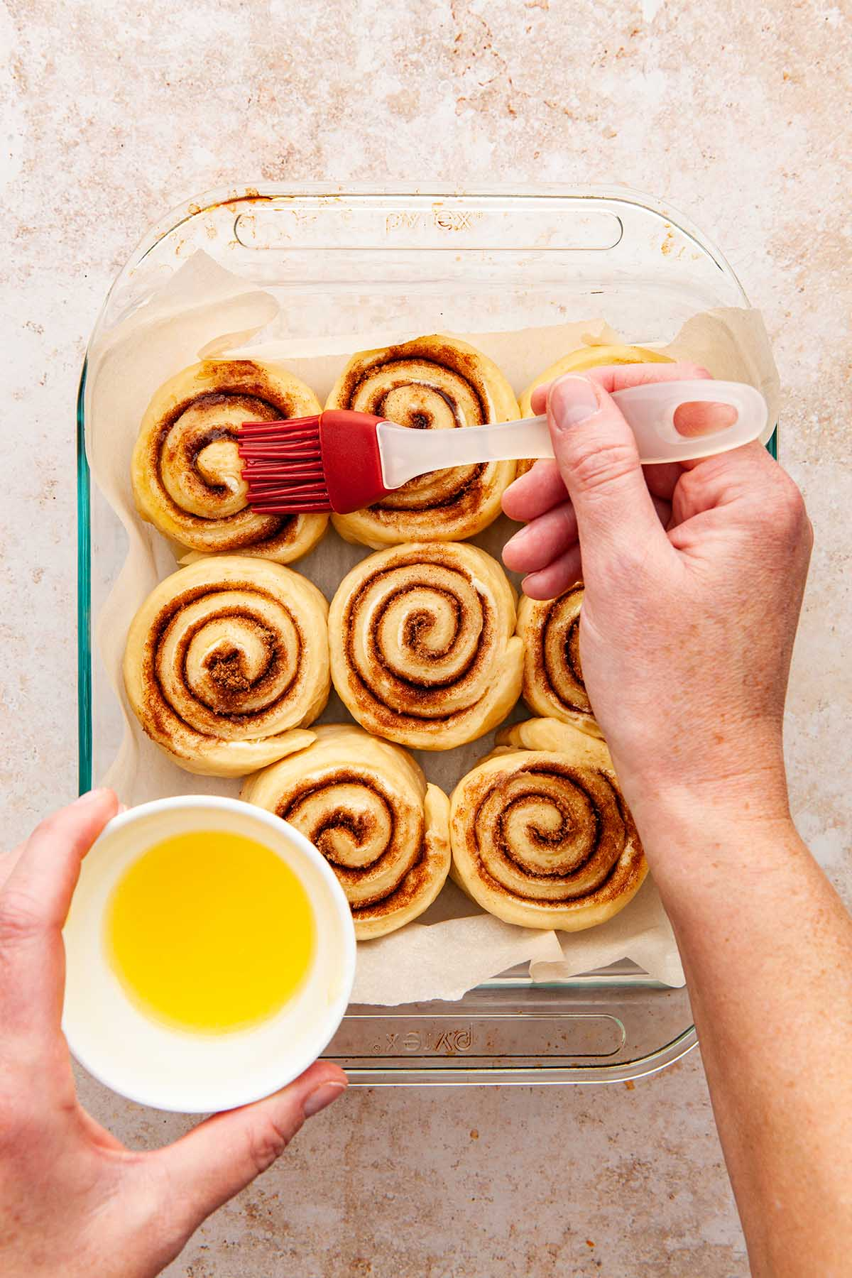 A hand brushing melted butter over the top of risen cinnamon buns.