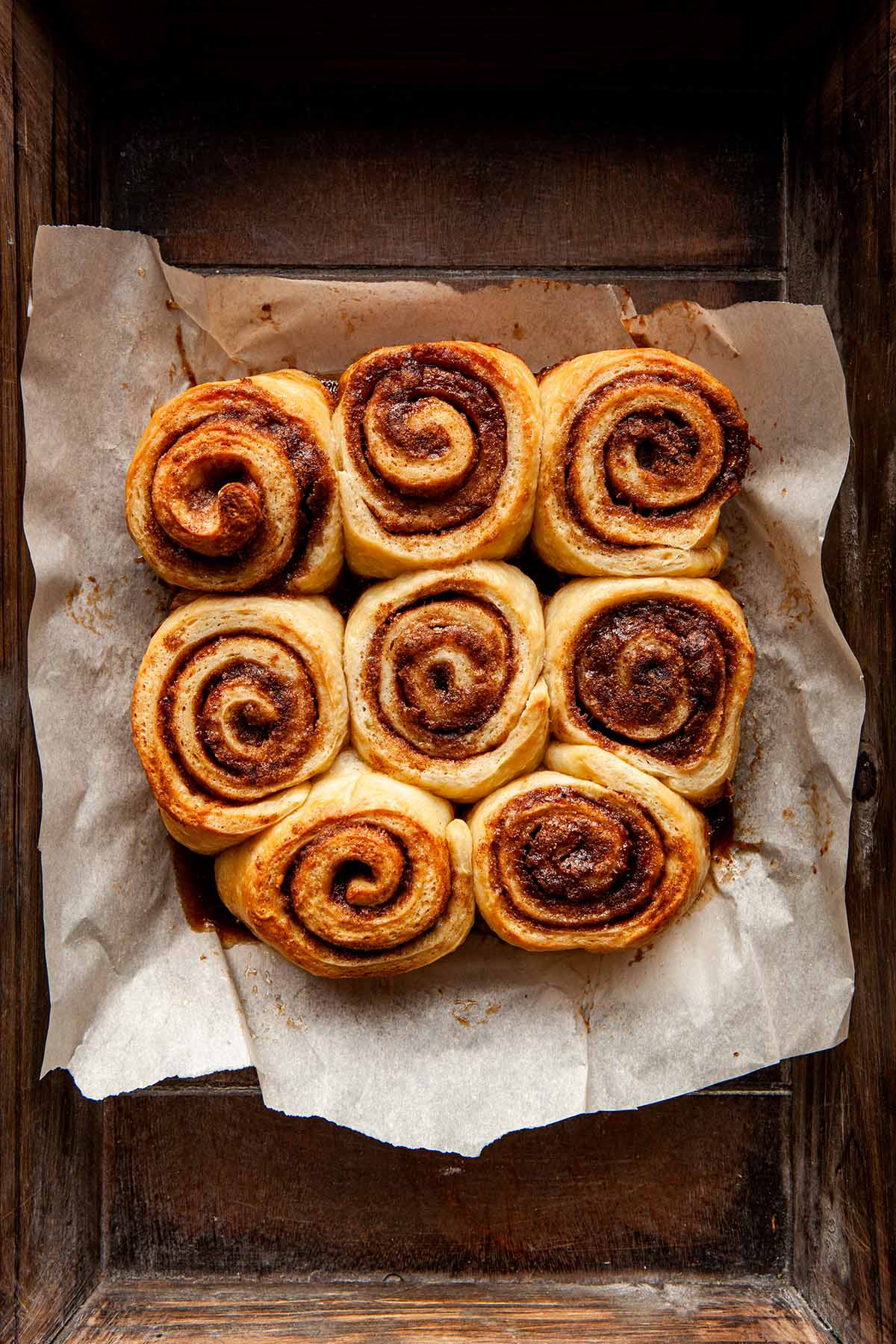 Small batch cinnamon rolls nestled together on the parchment paper they baked on, inside a wooden tray.