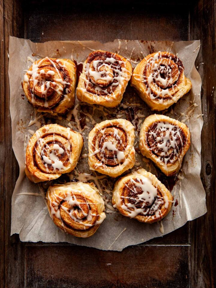Small batch cinnamon rolls drizzled with glaze on parchment paper inside a wooden tray.