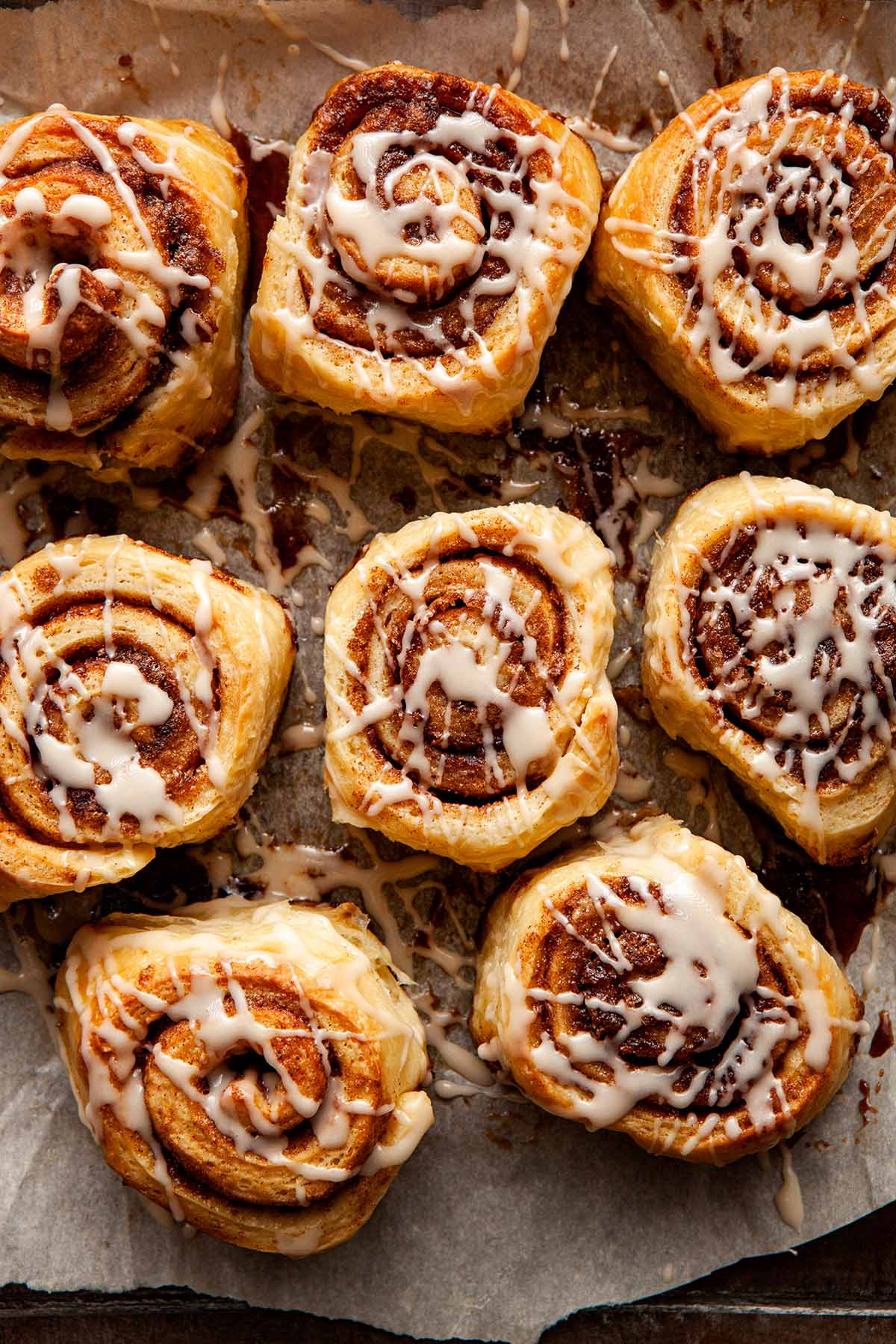 Overhead image of eight cinnamon buns drizzled with glaze.