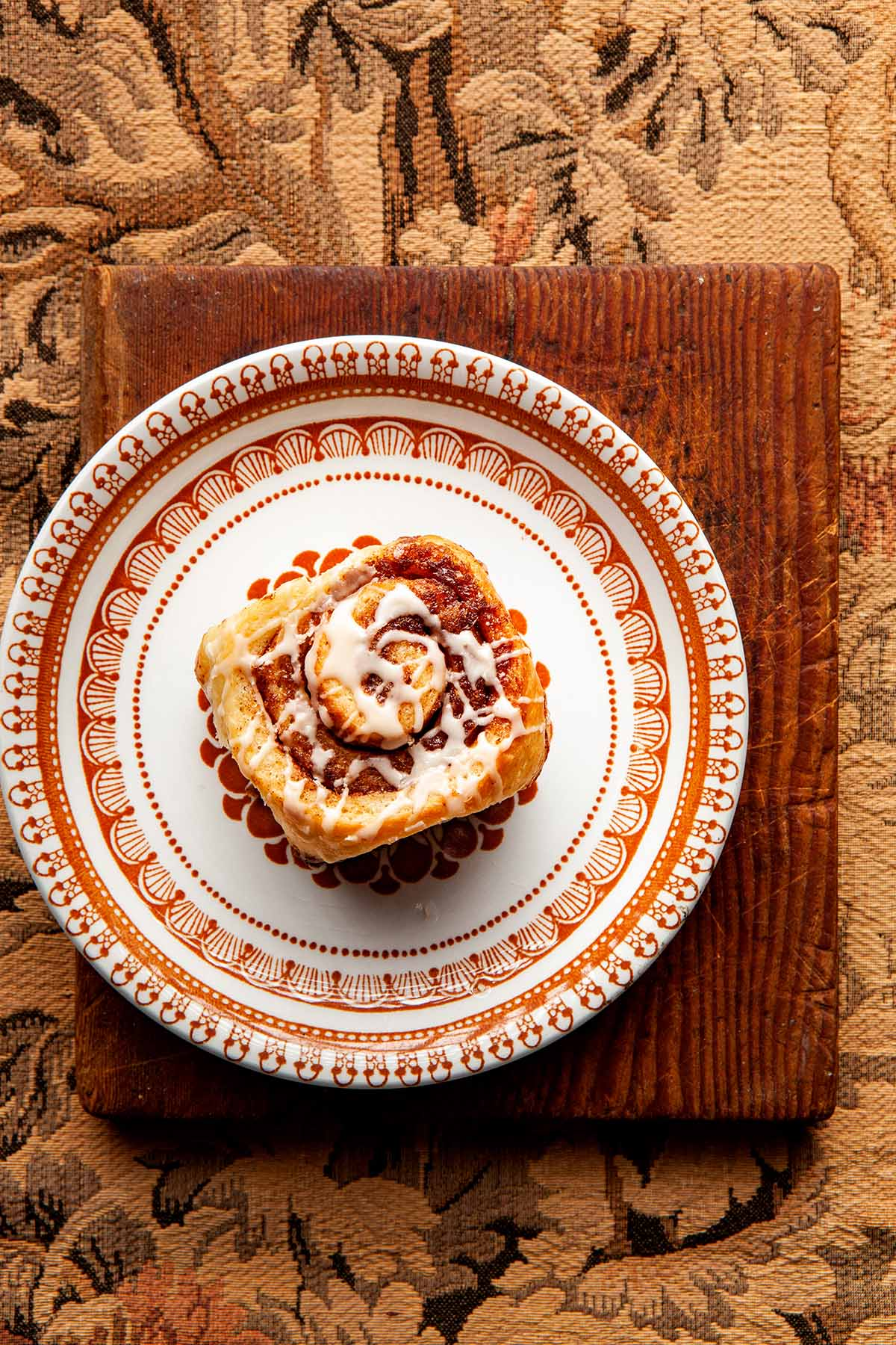 One cinnamon bun sitting on a retro orange and white plate, on top of a rustic cutting board, on beige tapestry fabric.