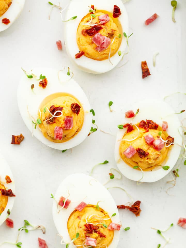 Close up of sriracha deviled eggs garnished with finely diced salami, finely diced sun dried tomatoes, and sprouts.