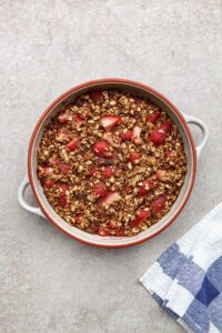 A pan of strawberry baked oatmeal on stone surface with a blue and white tea towel peeking in one corner.