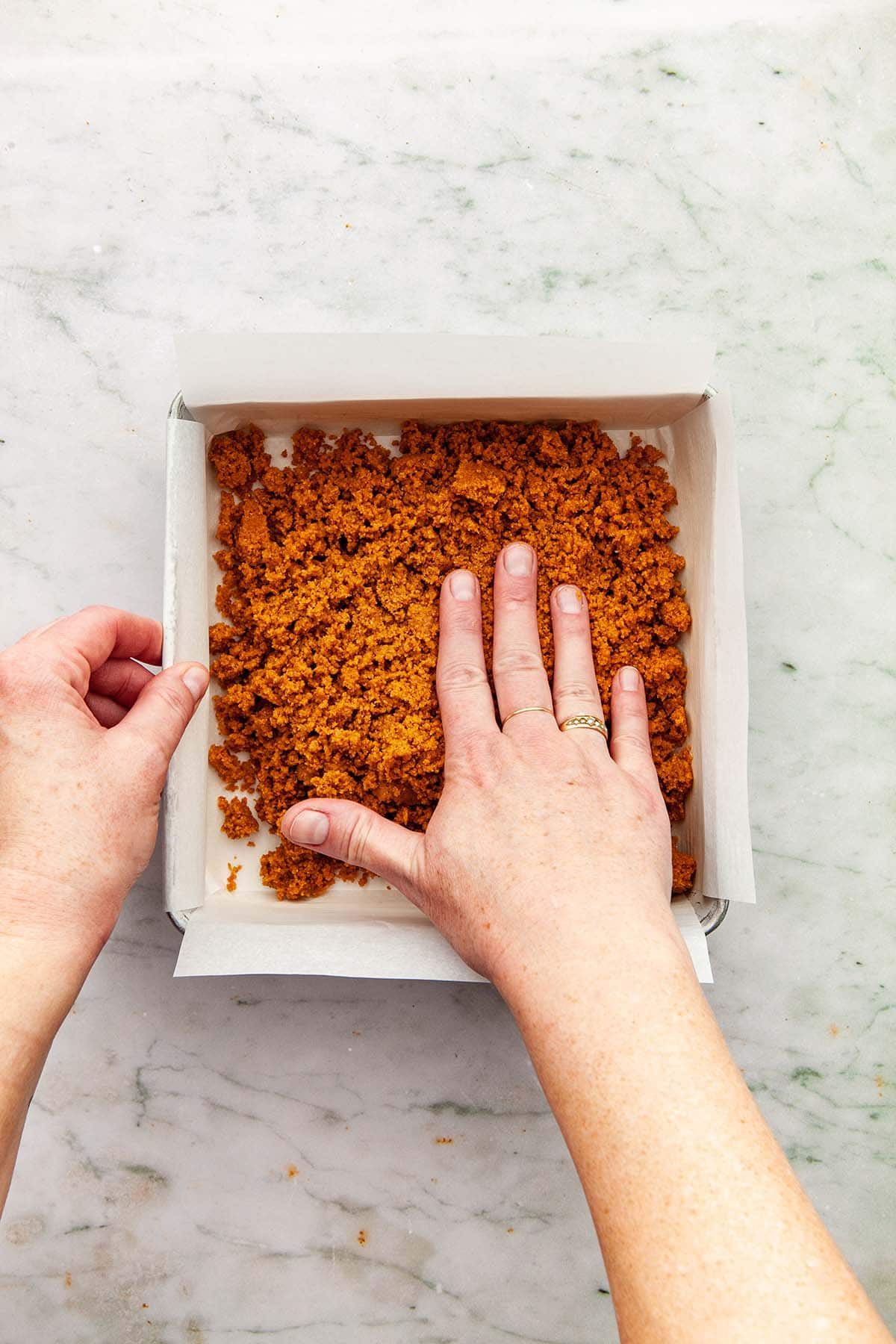 A hand beginning to press graham crumbs into a square pan.