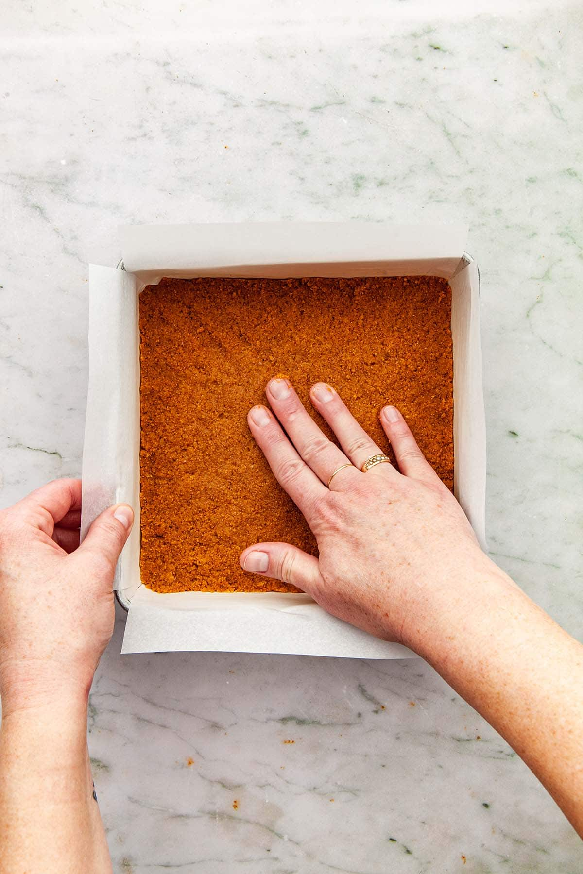 A hand finishing pressing graham crumbs into a square pan.