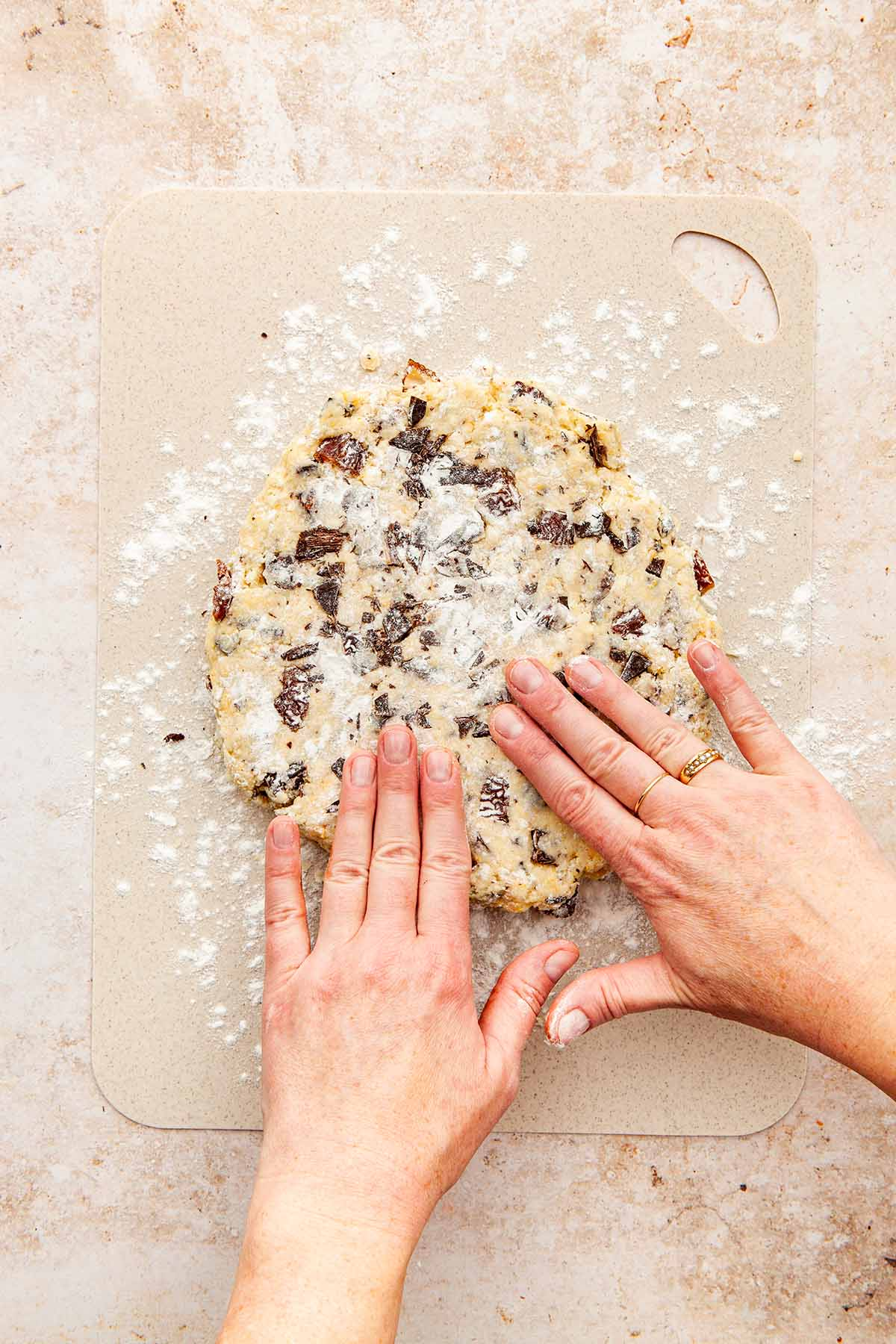 Hands pressing dough into a circle with fingertips.