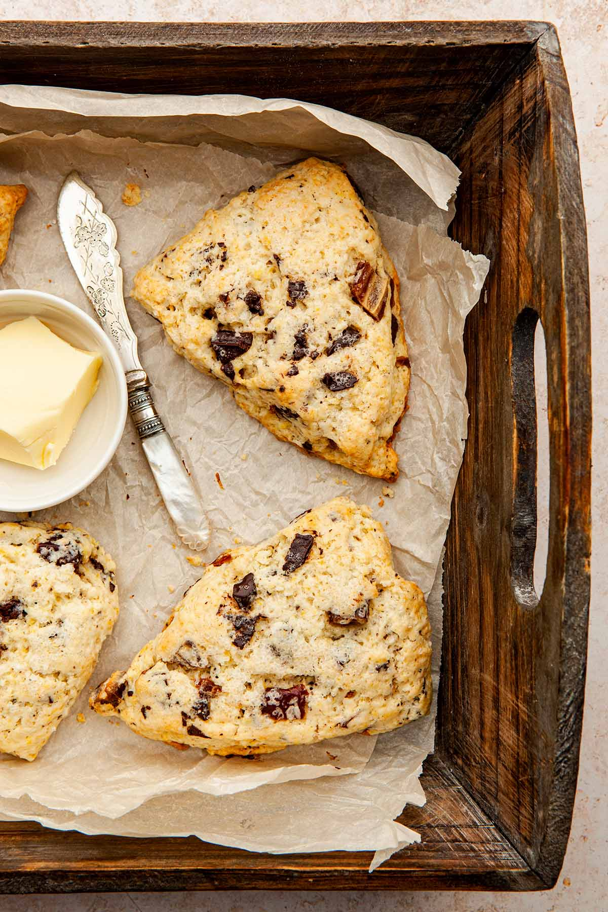 Two date and orange scones in a wooden box lined with parchment paper with a small dish of butter and a pearl-handled butter spreader.
