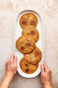 Two hands holding the sides of a long oval white speckled platter with five double chocolate spelt cookies on it.