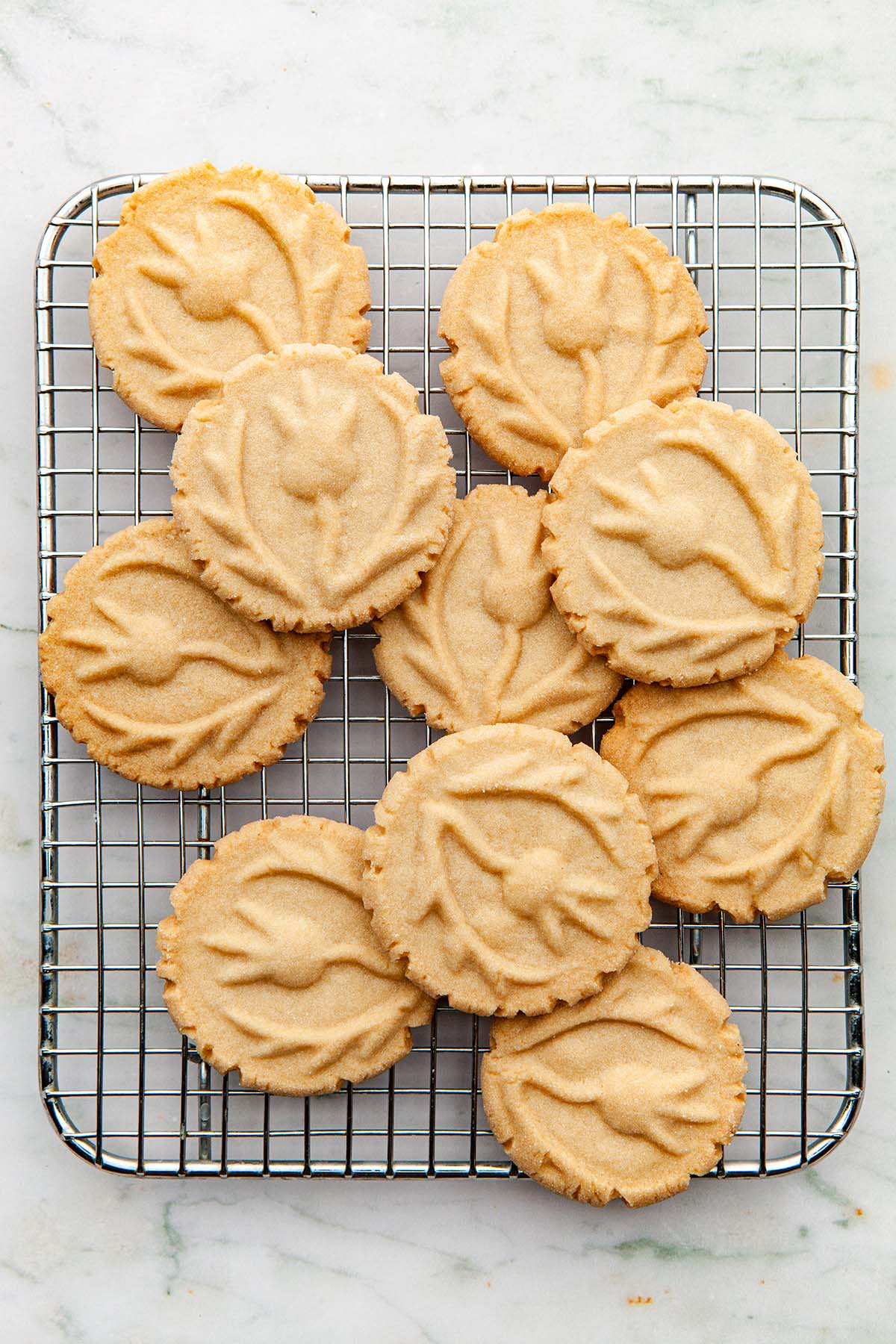 Stamped shortbread cookies on a wire cooling rack.