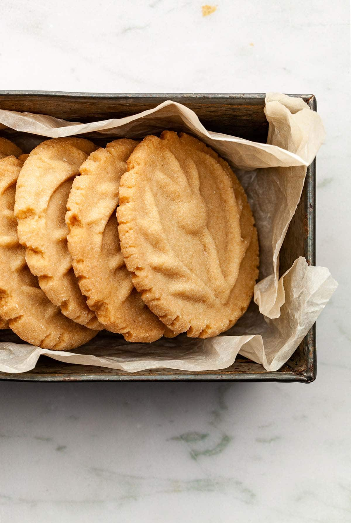 Stamped shortbread cookies stacked lengthwise in a small loaf tin lined with crumpled parchment paper.