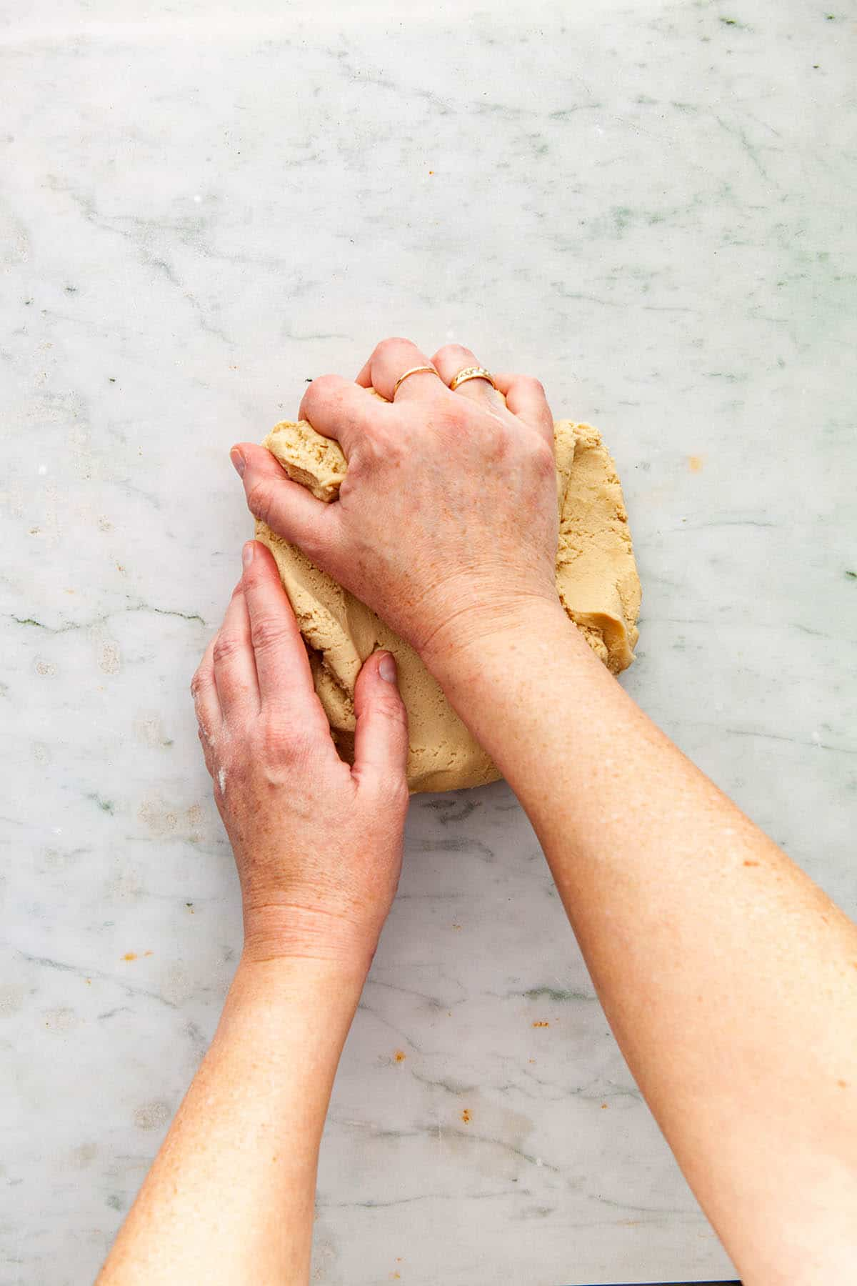 Hands kneading cookie dough.