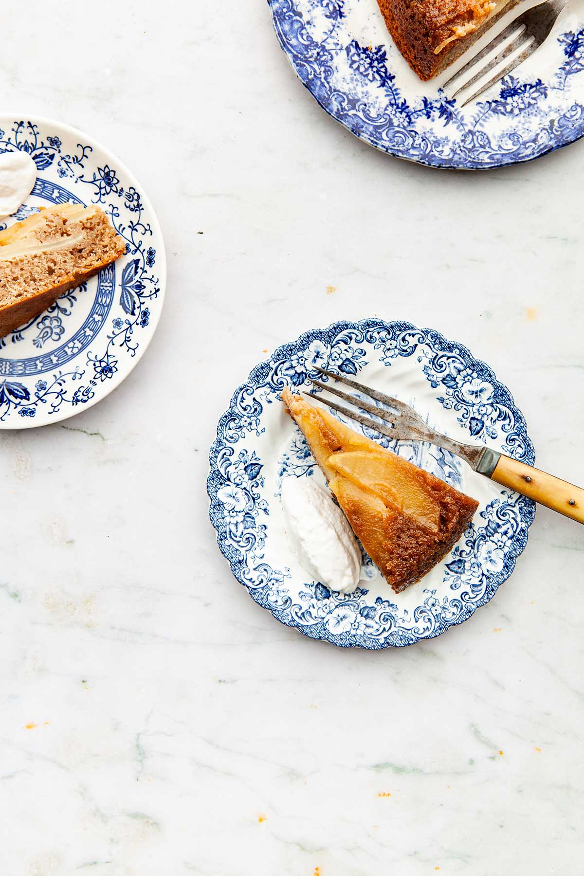 Overhead image of slices of chai cake on blue and white plates.