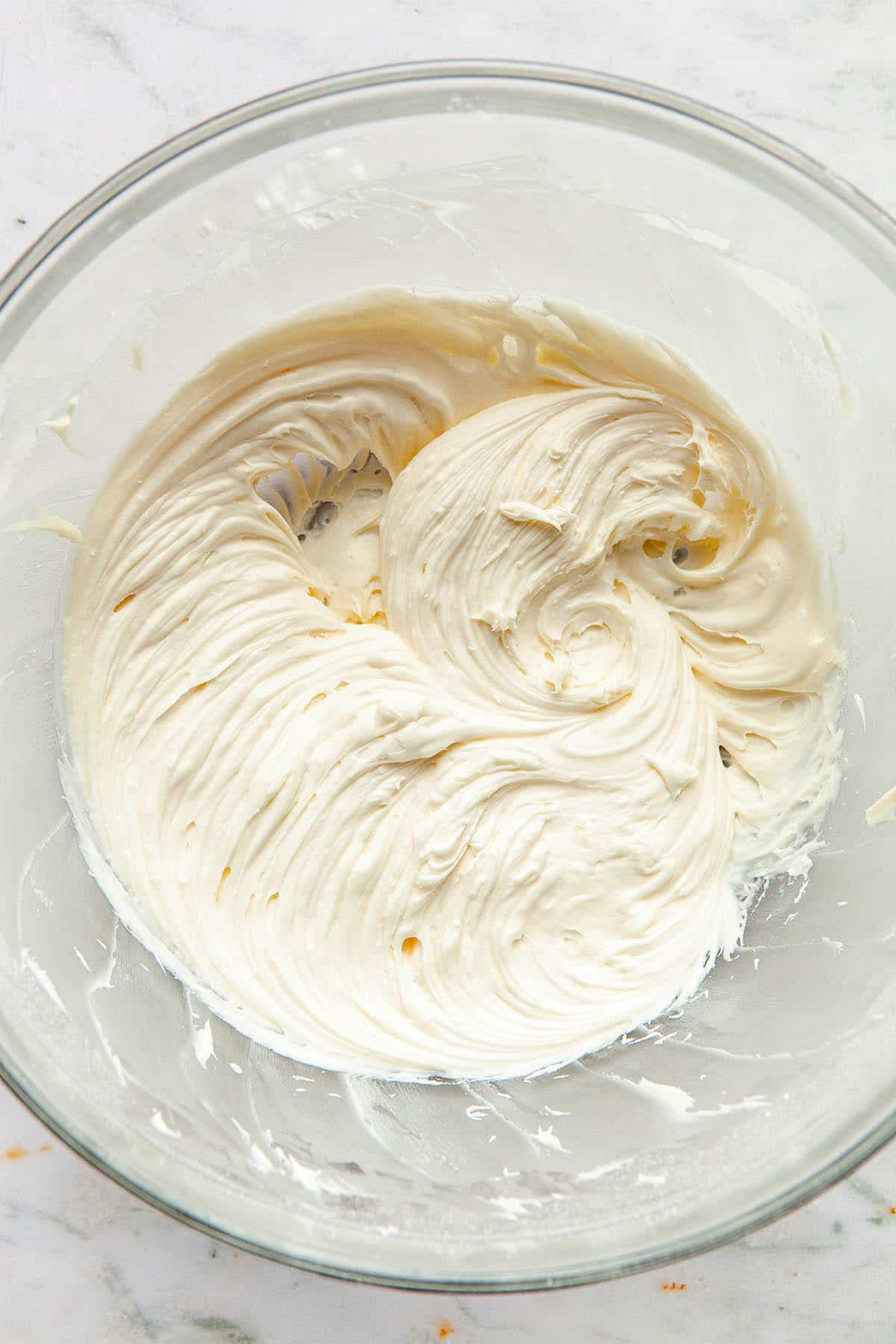 A large glass bowl of whipped cream cheese frosting.