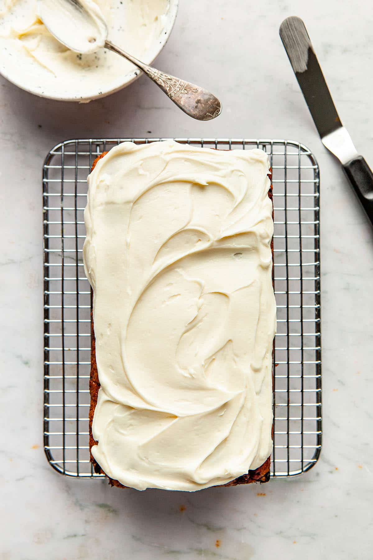 A baked loaf cake topped with swirls of whipped cream cheese frosting.