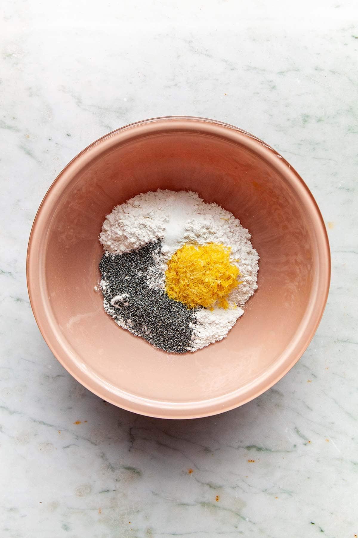 Flour, salt, poppy seeds, and lemon zest in a pink Pyrex bowl.