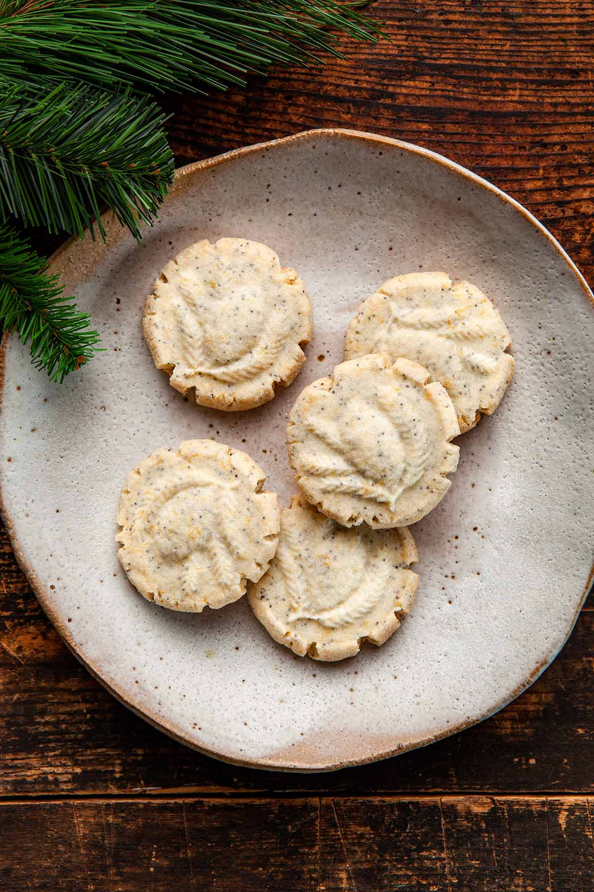 A plate of five lemon poppy seed shortbread cookies surrounded by evergreen branches.