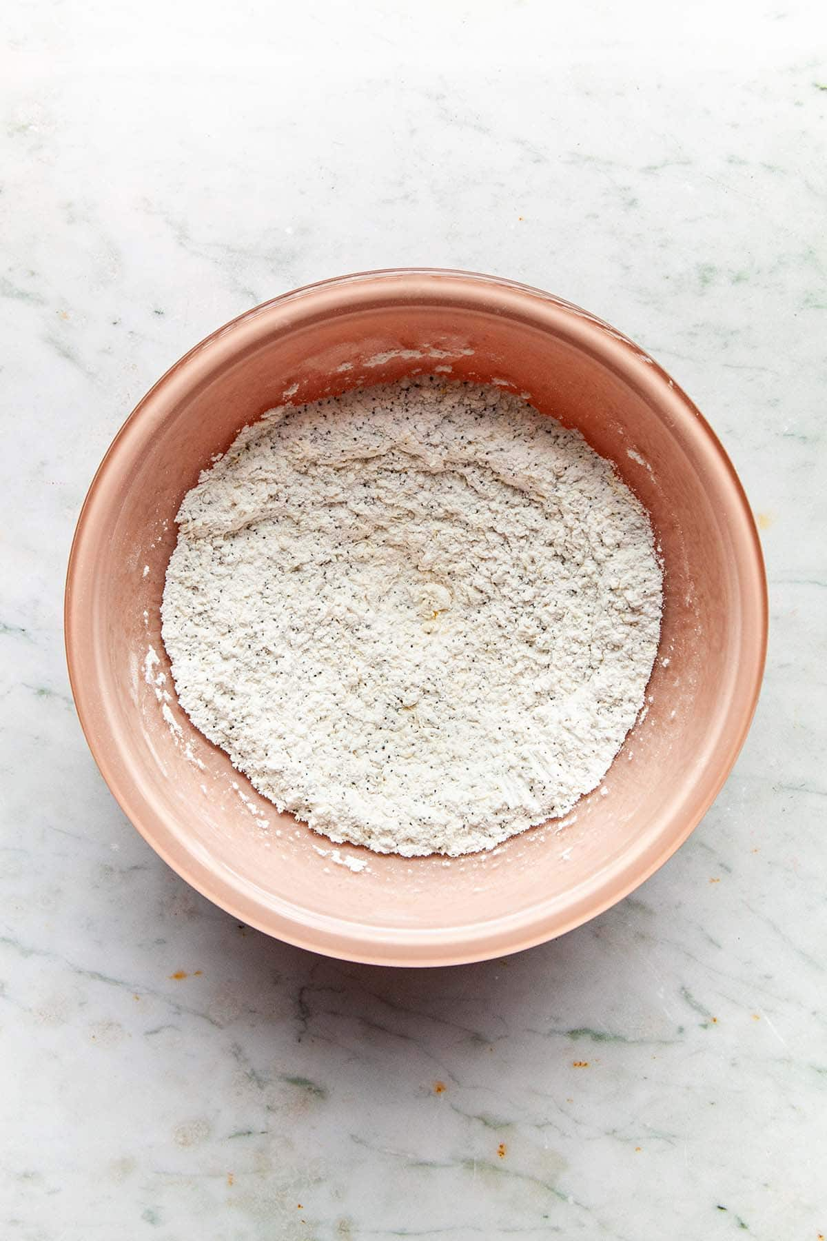 A bowl of flour mixed with poppy seeds.