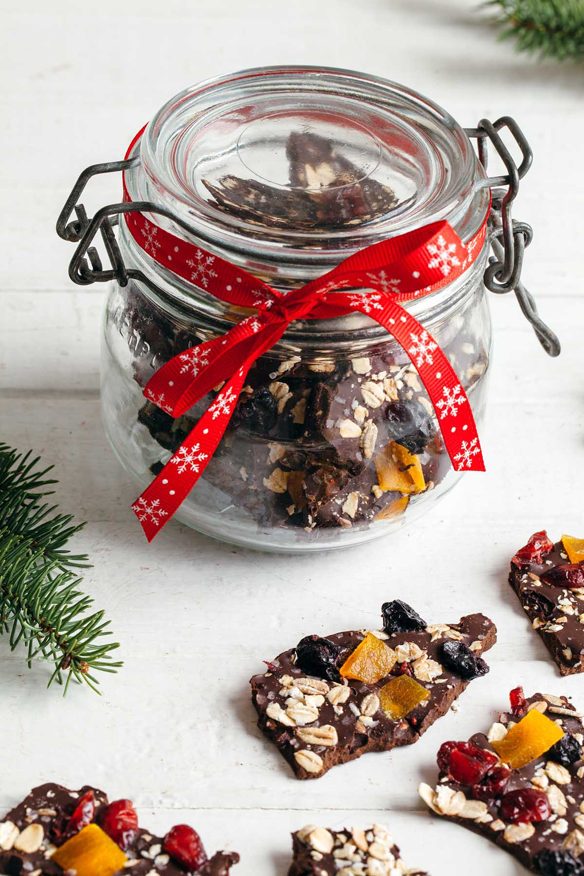 A glass jar of chocolate espresso bark tied at the top with a red ribbon.