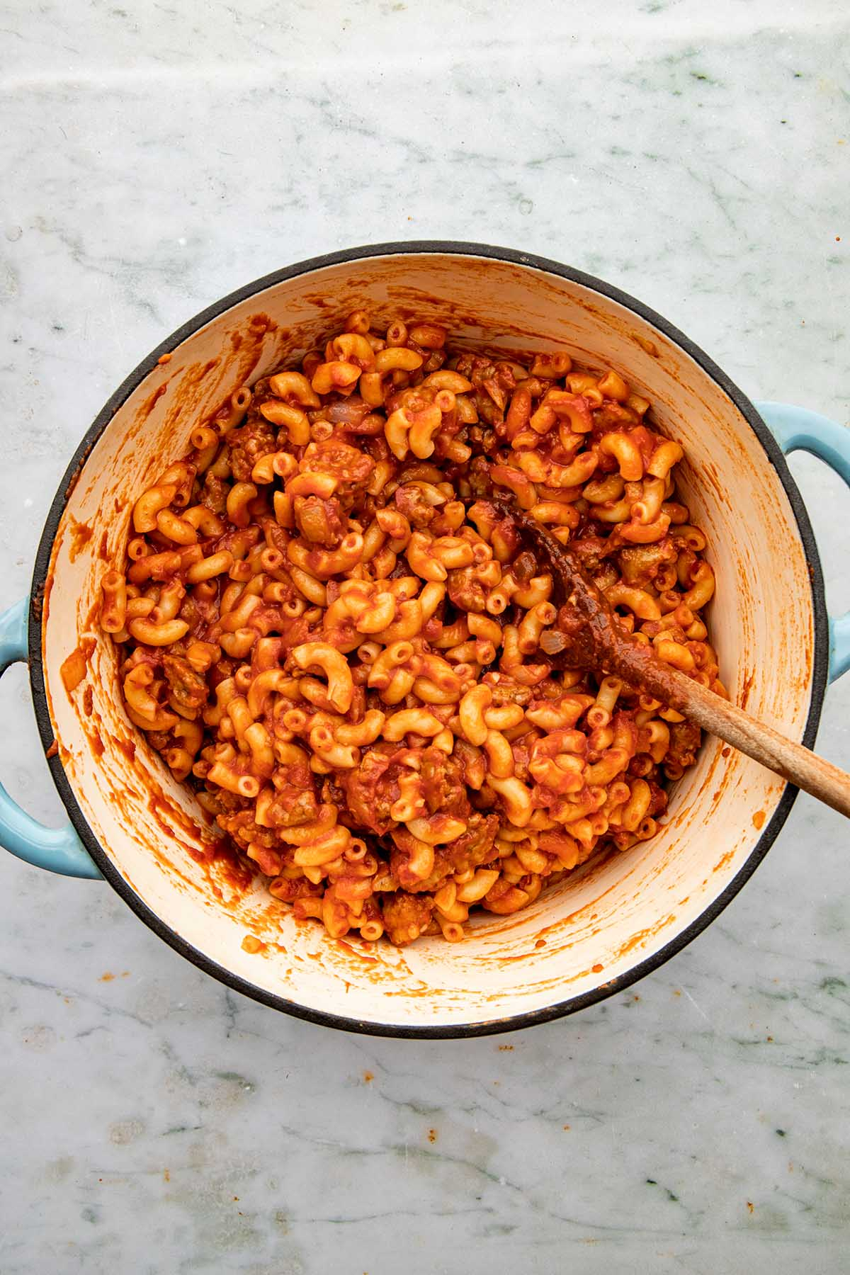A pot of cooked macaroni and tomato sauce with a wooden spoon in the pot.