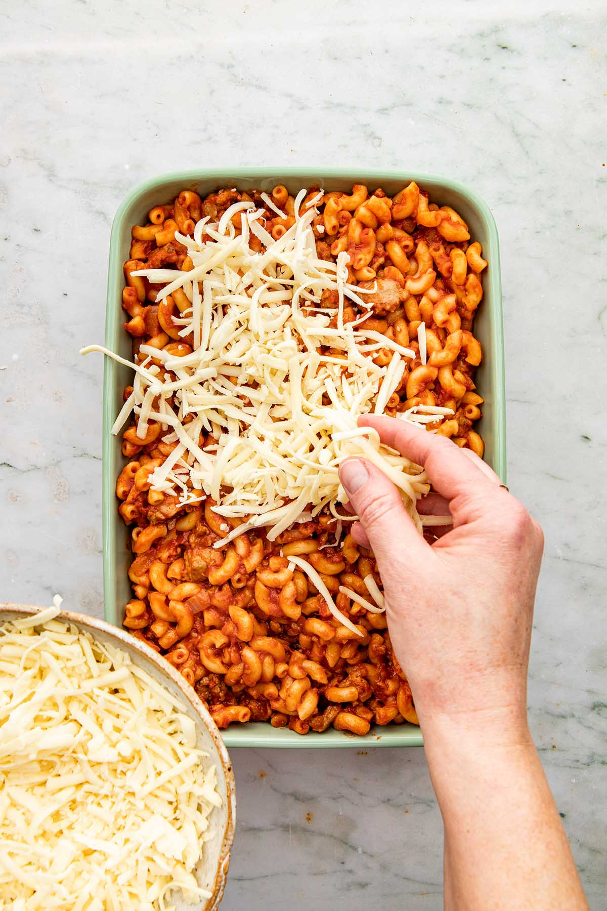 A hand sprinkling mozzarella cheese over pasta in a baking dish.