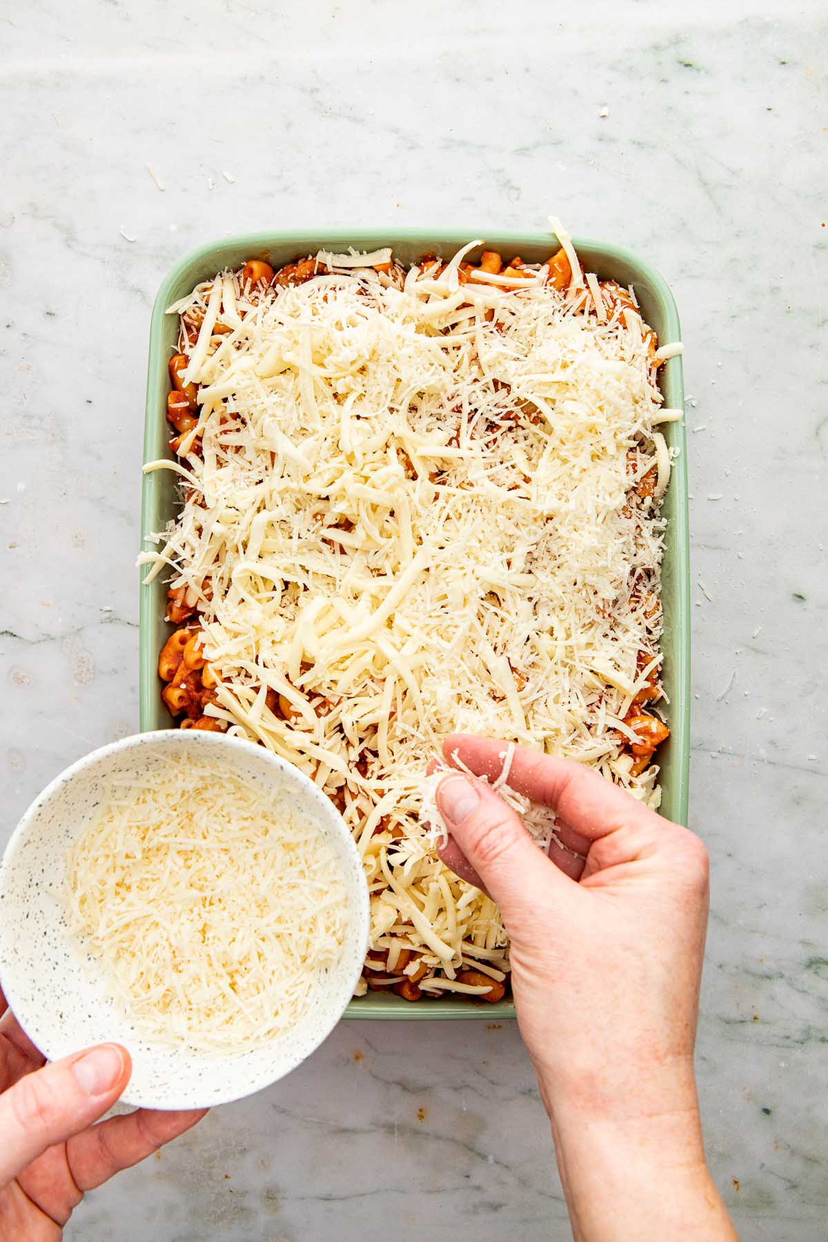 A hand sprinkling Parmesan cheese over pasta in a baking dish.
